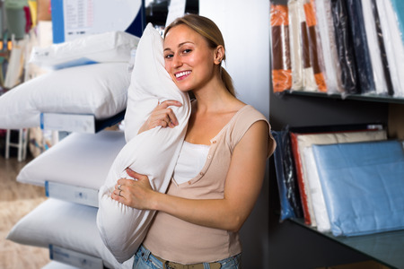 soft textile: ?woman customer picking soft pillow in textile department Stock Photo