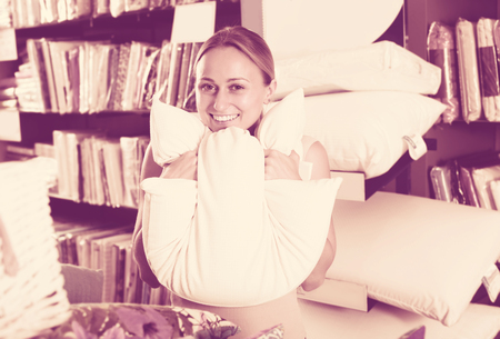 downy: Smiling woman customer holding downy pillow in home textile boutique Stock Photo