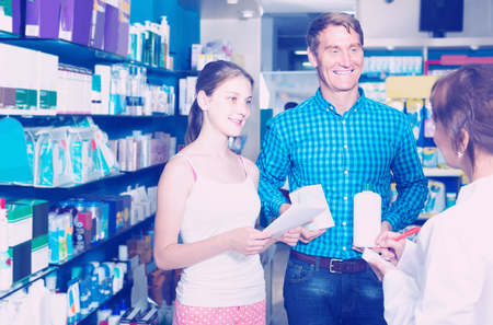 drug store: portrait of glad man with daughter teenager shopping medicine in drug store