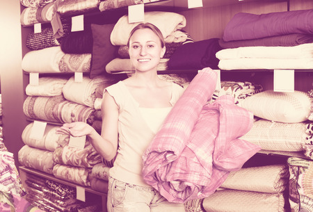 bedspread: joyful smiling young woman customer picking bed blanket in textile department