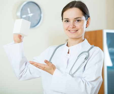 overall: Female therapeutist in white overall posing with box of supplement
