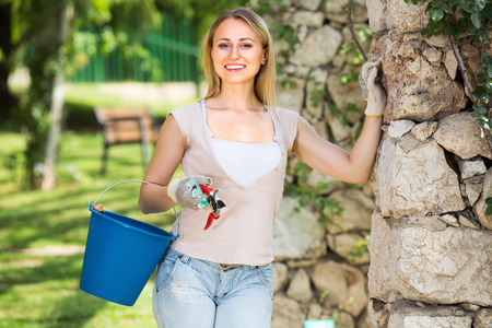 horticultural: hilarious young woman holding horticultural tools in garden on sunny day