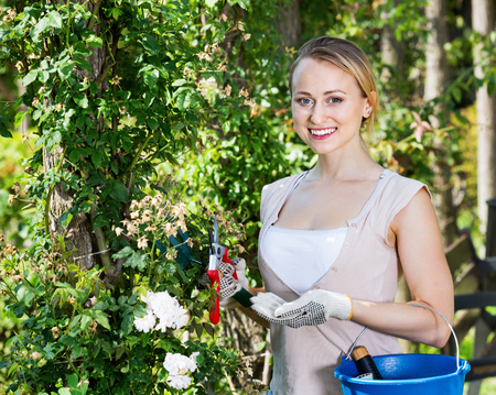 horticultural: Glad young blond woman having horticultural instruments in garden on summer day