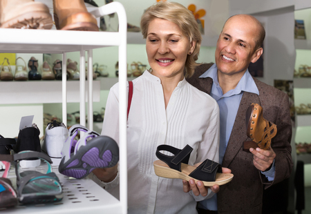 retirees: Two adult european  retirees together choosing pair of shoes in fashion store