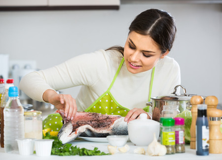 jorobado: Happy european girl eviscerating salmon fish in domestic kitchen Foto de archivo
