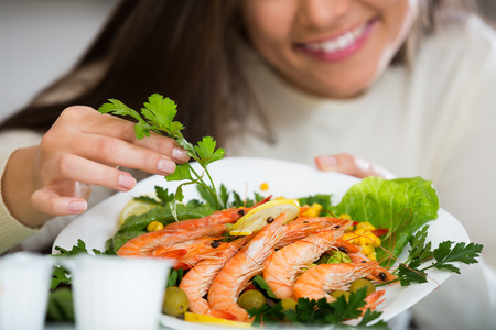 jorobado: Smiling brunette in white pullover decorating plate with fried prawns at home kitchen. Focus on plate