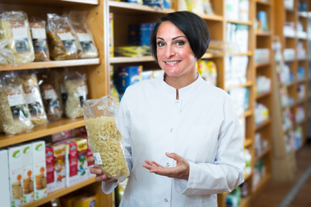 shelfs: Smiling mature woman seller in uniform holding cereals products in hands near shelfs
