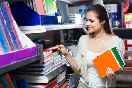 ?smiling woman shopping notebooks and writing paper in stationary store Imagens