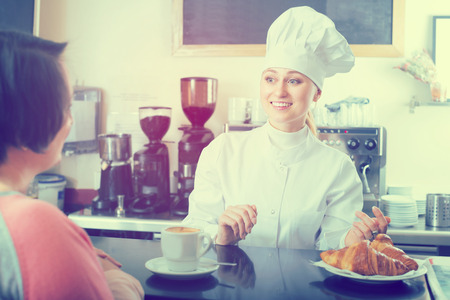 gladly: Happy young female cook gladly selling pastry to a customer in the cafeteria