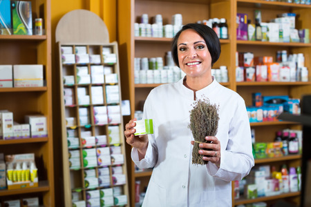 smiling  mature woman in white coat standing with bunch of dried vulnerary herbs in drugstore