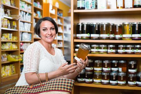 mature brunette: Smiling mature brunette woman choosing honey from assortment in drugstore