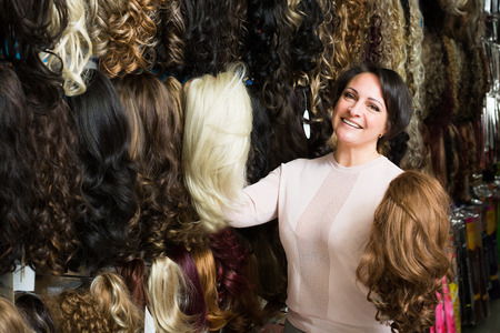 chignon: portrait of happy woman looking at different color hair extensions in shop Stock Photo