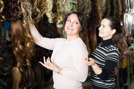 purchasers: Friends buying clip-in natural hair extension at store Stock Photo