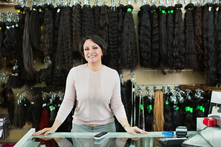 chignon: Shop woman posing at counter with artificial and natural hair Stock Photo