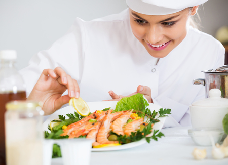 jorobado: chef profesional feliz que adorna filetes de trucha al horno de arco iris