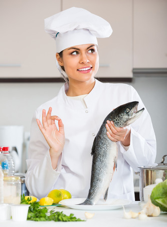 corcovado: Smiling young female chef cooking rainbow trout in commercial kitchen