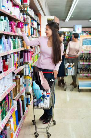glad: Glad smiling female customer selecting drugstore products and standing with shopping trolley