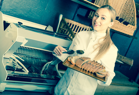 automatically: Merry young girl dressed as baker showing automatically cut bread in the bakery Stock Photo