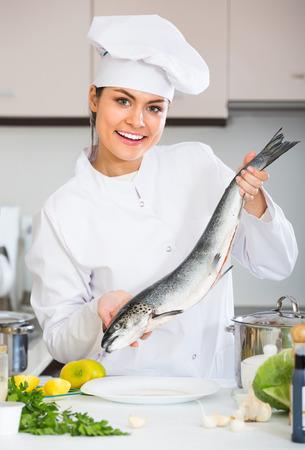 jorobado: Sonriendo cocinera cocinar la trucha arco iris en la cocina comercial