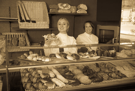 gladly: Happy woman and young girl gladly selling pastry in the cafe Stock Photo