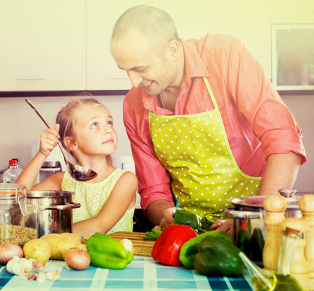 a little dinner: Little girl helping father to prepare dinner in domestic  interior