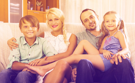 clase media: Portrait of happy middle class caucasian family at home interior. Focus on boy