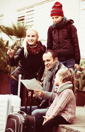 middle class: familia de clase media de cuatro miembros feliz dirección de verificación en el mapa al aire libre Foto de archivo