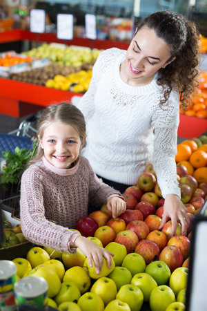purchasers: Portrait of happy smiling young woman and little daughter buying ripe apples at the market Stock Photo