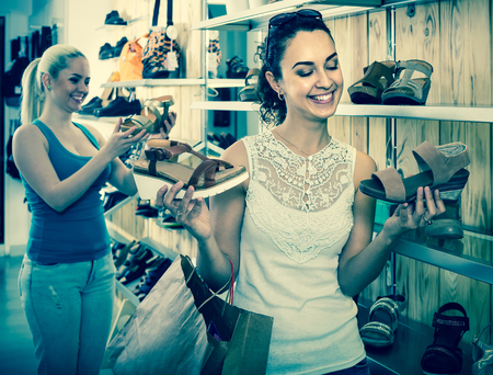 spanish girl: happy spanish girl holding a picked pair of shoes in the boutique