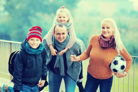 clase media: retrato al aire libre de la familia feliz con el hijo y la hija Foto de archivo
