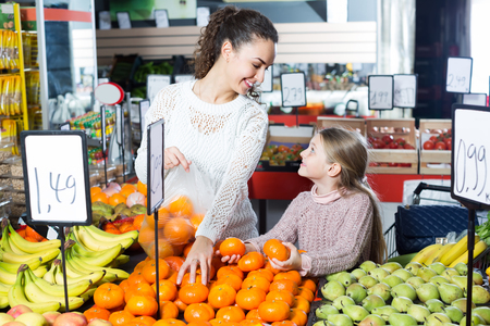 purchasers: Smiling young woman and little girl buying fruits in grocery food store