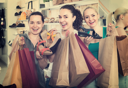comprando zapatos: Tres muchachas sonrientes alegres que compran nuevos zapatos de verano en la tienda de moda