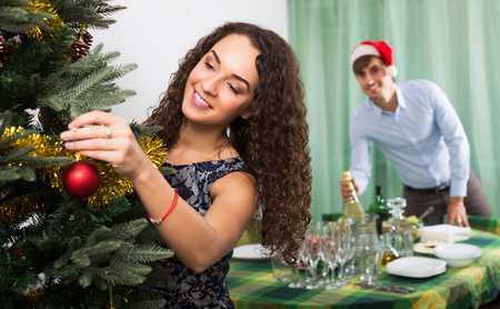 home decorating: Young couple decorating Christmas tree and serving  festive table in home