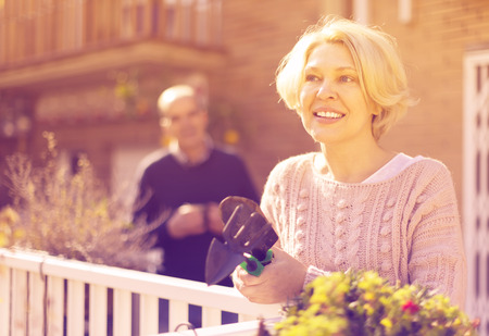 Joyful smiling mature woman with horticultural sundry and aged man drinking tea in patio Stock Photo