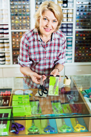 glad: Portrait of mature glad cheerful female cashier standing at cash desk with scissors in shop
