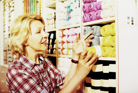 glad: Glad mature woman selecting colorful yarn in sewing store