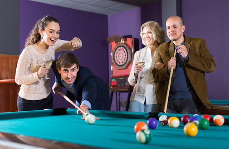 Smiling middle class adults having pool game in billiard club. Selective focus