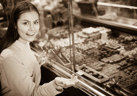 Smiling brunette girl buying dark and white chocolate with fillings Stock Photo
