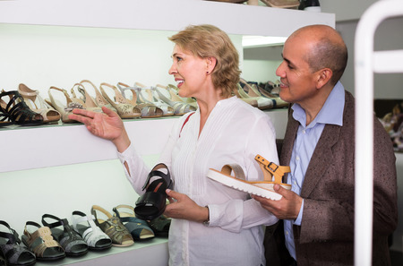 retirees: Two positive european retirees together choosing pair of shoes in fashion store