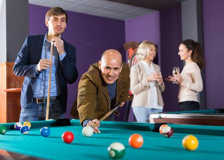 clase media: las personas de raza blanca de clase media positivos que tienen piscina juego en el club de billar