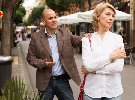 argumentation: Portrait of annoyed mature woman standing away from arguing man outdoors Stock Photo