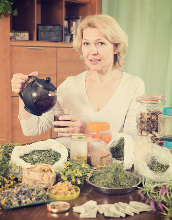 concoct: Senior  woman drinking herbal tea and smiling