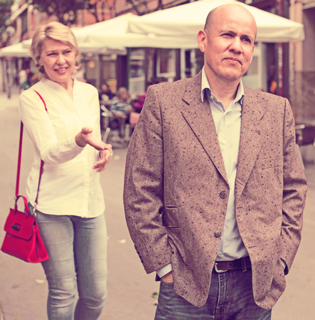 argumentation: Portrait of annoyed mature man standing away from arguing woman outdoors