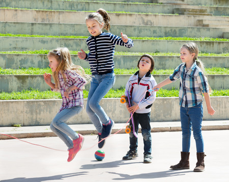 Young girl jumping while jump rope game with friends outdoor 스톡 콘텐츠