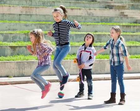 Jong meisje die terwijl springtouwspel met vrienden openlucht springen