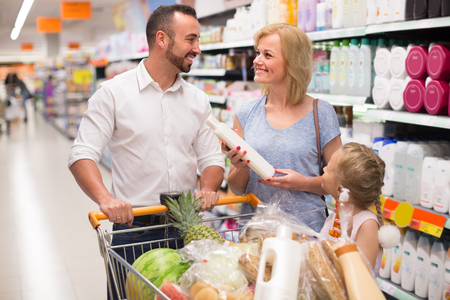hypermarket: Happy smiling young family with trolley selecting shampoo  in supermarket