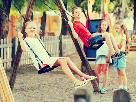 frisky: View on happy glad frisky children swinging together on childrens playground in town Stock Photo