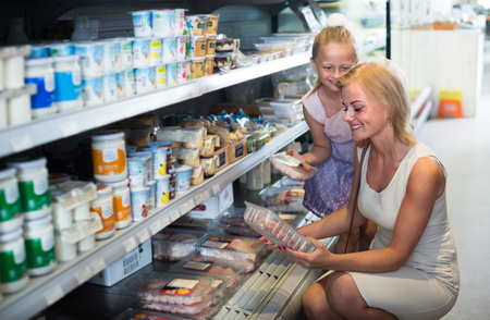 refrigerated: smiling blonde woman and girl buying meat in refrigerated section in food store. Focus on woman Stock Photo