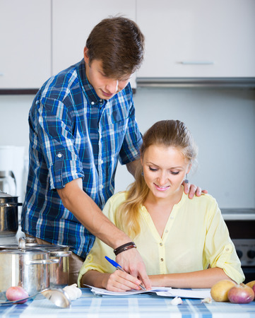 positive spouses signing documents and smiling at kitchen