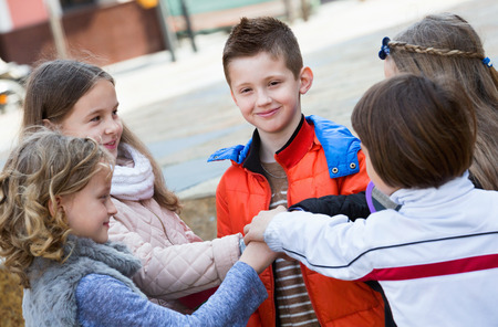 vow: Positive happy smiling children holding hands and giving friendship vow
